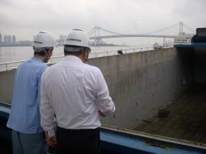 内航船の荷役風景を見学する学生と、アテンドする小林所長