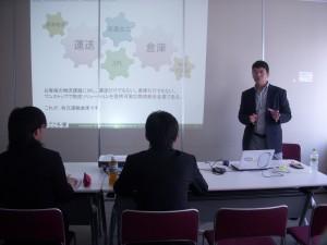 弊社のビジネスについて説明する坂田。