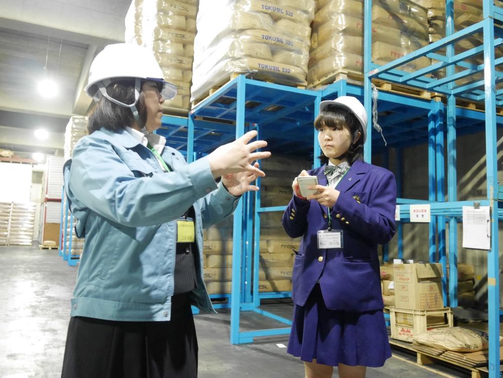 朝日新聞に掲載された写真。弊社倉庫内にて、説明を行う弊社:上田と、熱心にメモを取りながら話を聞くあおやまさんの様子。