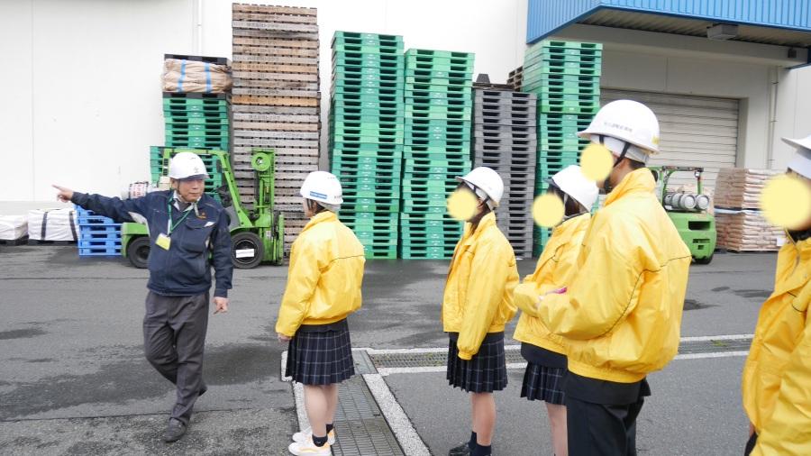 高校生を引率して倉庫見学をする当社部長:小林。